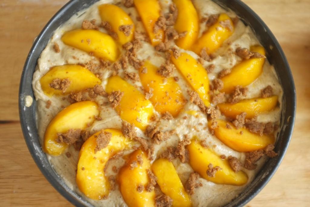 Le gâteau avant cuisson vu de dessus, pêches et crumble de sucre à la cannelle