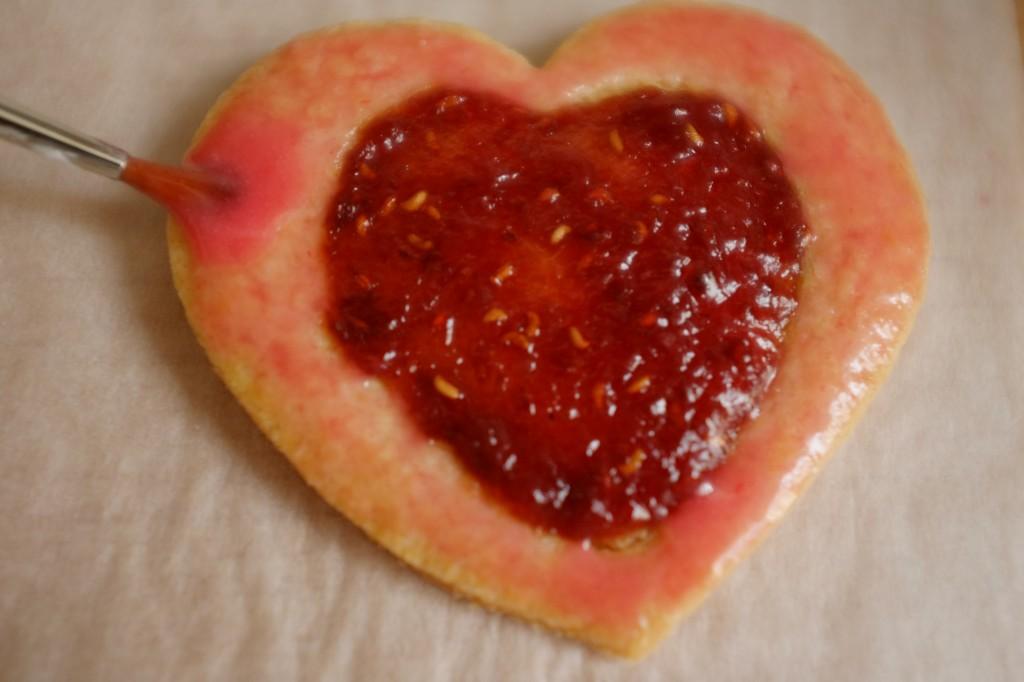 Le glaçage coloré à la framboise est déposé sur les bords du biscuit à l'aide d'un pinceau