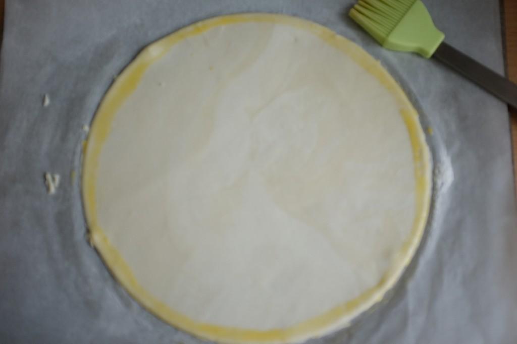 Sur la pâte du fond, à l'aide d'un pinceau en silicone, je passe du glaçage qui va servir à coller la bordure.