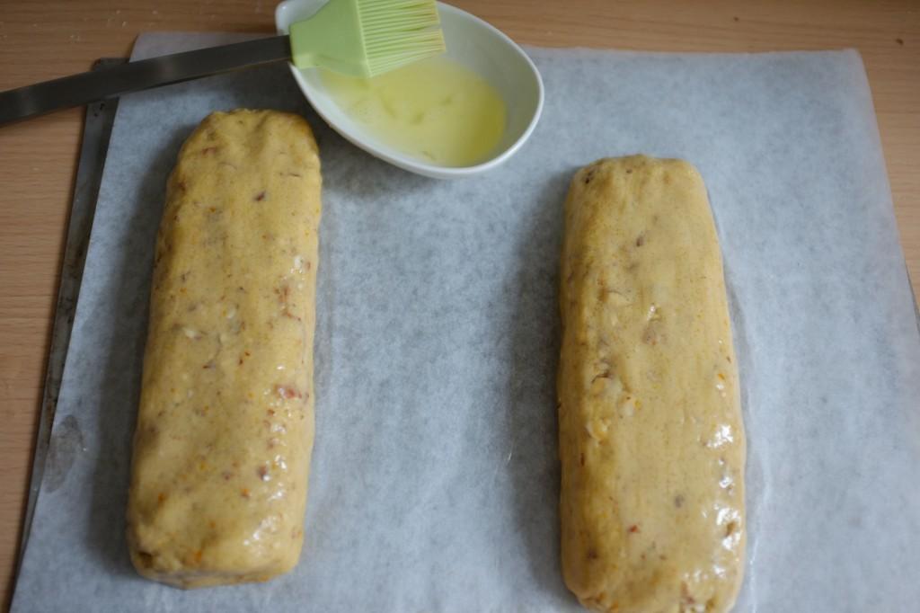 Les pains sans gluten de biscotti, badigeonnés de blanc d'oeuf avant d'être enfournés
