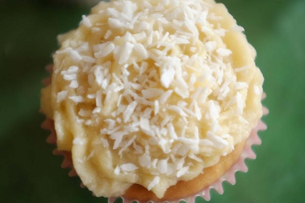 Je saupoudre le cupcake sans gluten et la crème au beurre de noix de coco râpée