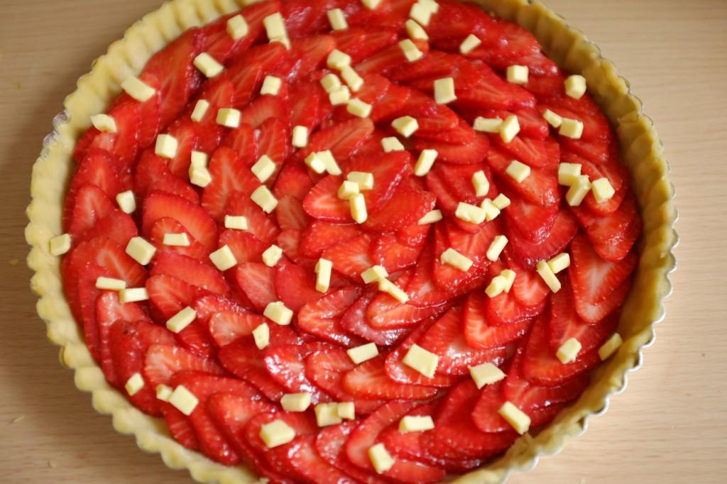 Les fraises sont saupoudrées de sucre et de petits morceaux de beurre