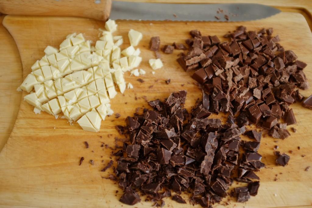 """Les 3 chocolats sans gluten sont coupés au couteau à pain pour obtenir les parfaits """"éclats de chocolat"""" pour décorer les cookies."""