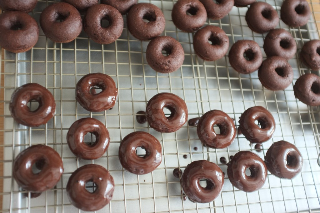 Les mini donuts sans gluten en train d'être glaçés au chocolat