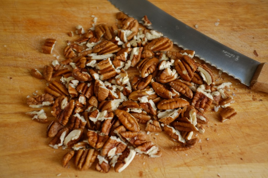 Les noix de pécan sont coupées en orceaux à l'aide d'un couteau à pain