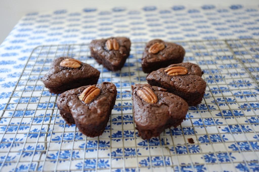 La première fournée des petits brownies aux noix de pécan refroidissent sur une grille