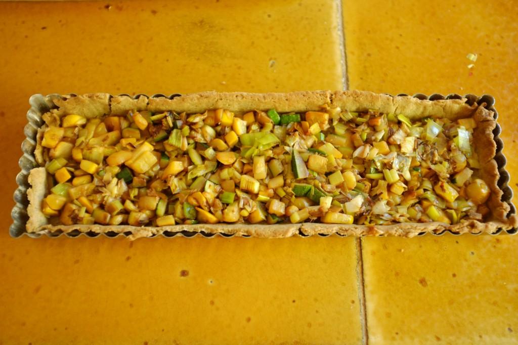 Le fond de tarte sans gluten est rempli de courgettes et poireaux