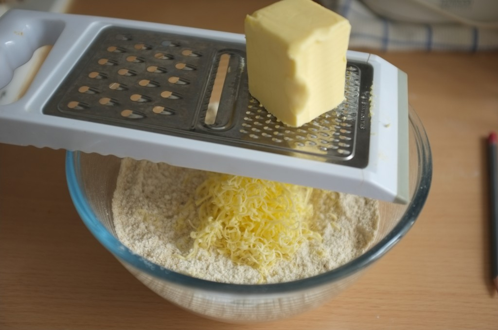 Le beurre congelé est rapé au dessus des ingrédients secs tamisés