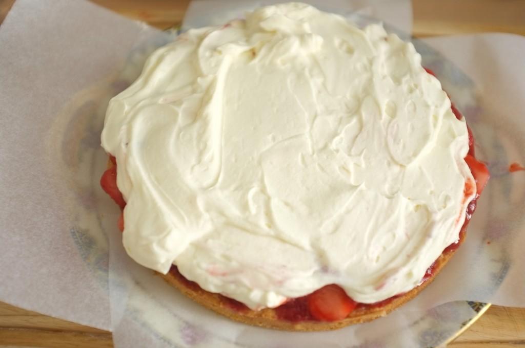 La crème fouéttée est généreusement étalée sur les fraises