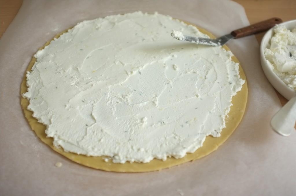 Je tartine le fond de pâte sans gluten avec le fromage de chèvre parfumé