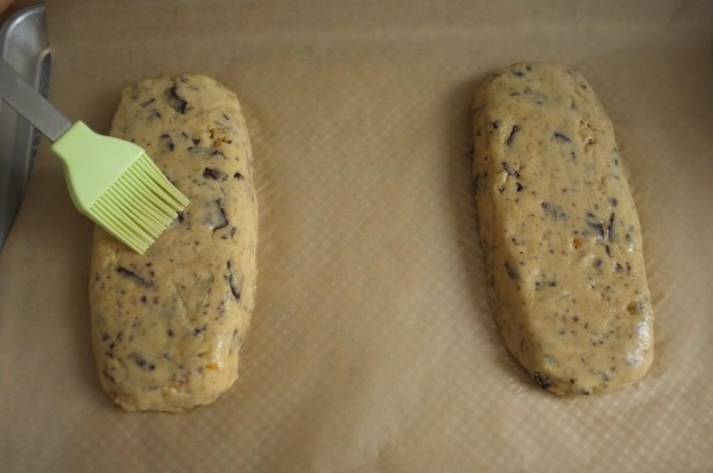 Les pains de biscotti sont badigeonnés d'un blanc d'oeuf battu