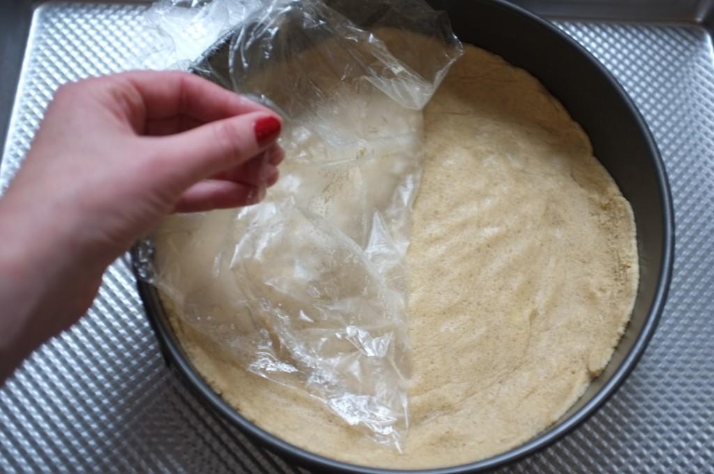 Pour étalerfacilement la pâte sans gluten au fond du moule, j'appuie sur la pâte avec une feuille de film fraîcheur
