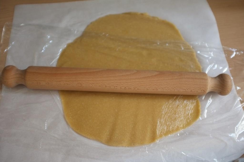 La pâte sans gluten pour les biscuit Hamantaschen, que j'étale antre une feuille de papier cuisson et une feuille de film fraicheur.