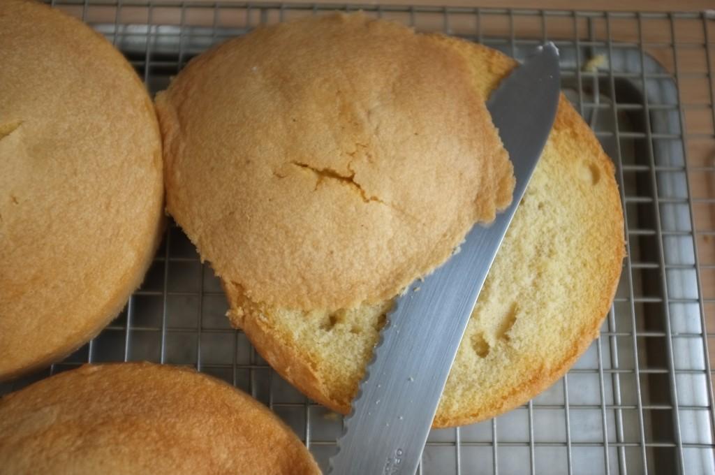 Je coupe, à l'aide d'un couteau à pain, le dessus de chaque gâteau pour laisser apparaitre la génoise sans gluten.