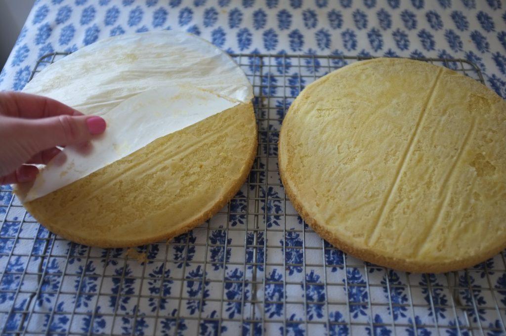 Les génoises sans gluten refroidissent sur une grille, je retire délicatement la feuille de papier cuisson qui est resté collée.