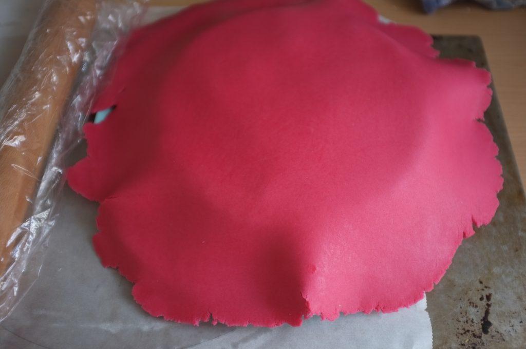 La pâte à sucre est enfin déposé sur le gâteau, on apperçoit le rouleau à pâtisserie emballé dans le film alimentaire
