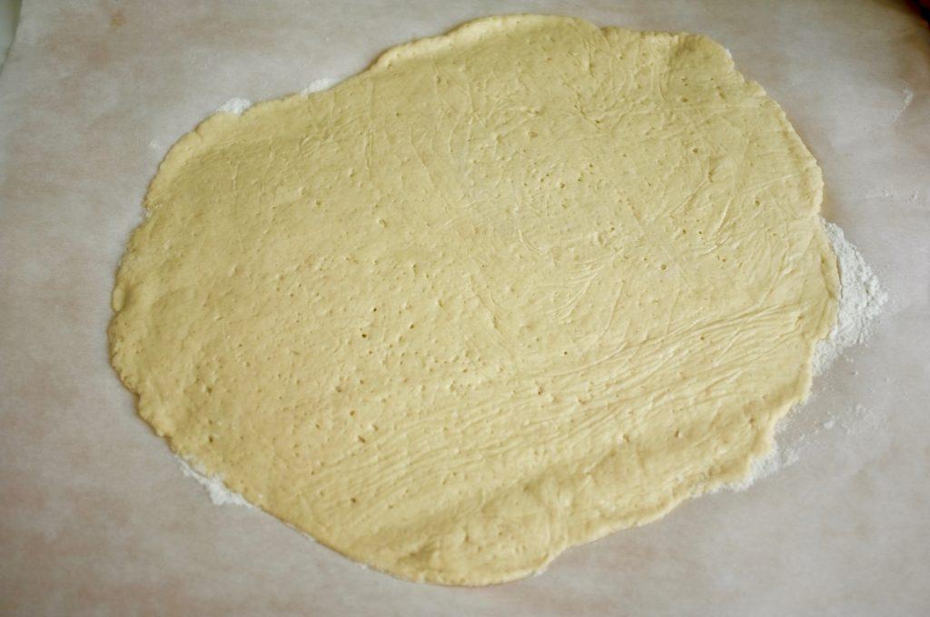 """La pâte à pizza sans gluten étalée, prête à être cuite """"à blanc""""."""