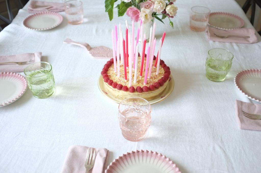 Mon gâteau d'anniversaire sans gluten à deux étages, parfumé à la vanille et décoré de framboises fraiches.
